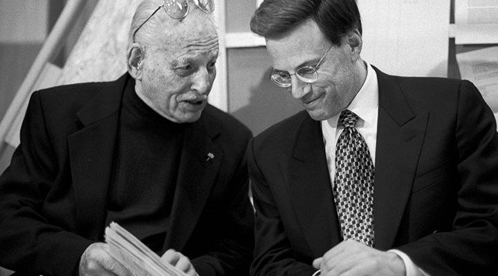 Two men converse over a notebook