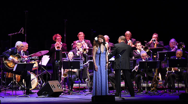 Solo vocalist performs, accompanied by a full jazz band with Burrell on guitar