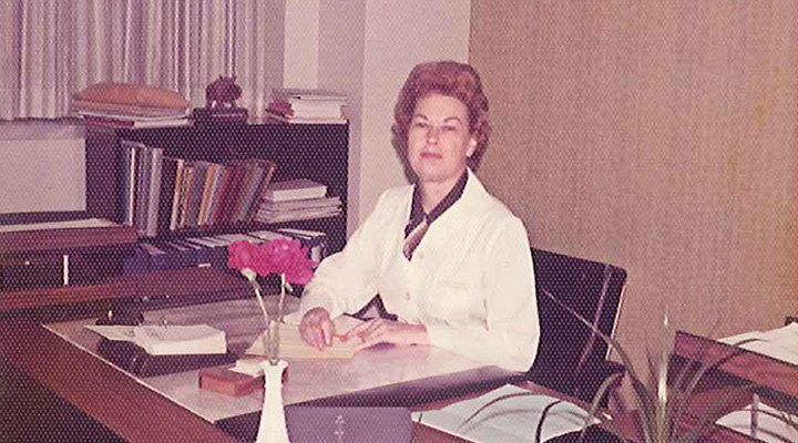 Studer, in her white lab coat, poses over paperwork at her desk