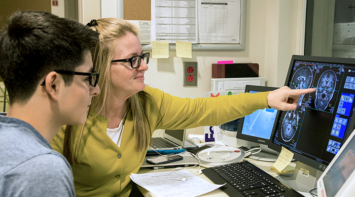 Students study brain images on a computer screen