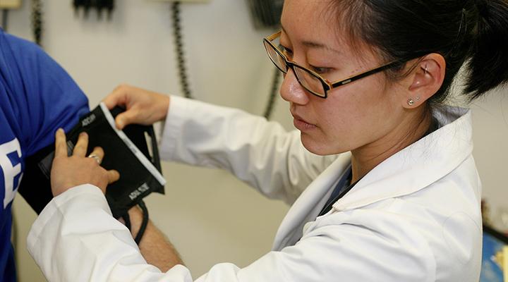 Student nurse wraps a blood pressure cuff around a patient's arm