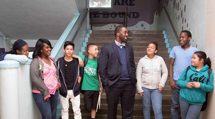 Principal shares a laugh with students gathered at the foot of the stairs