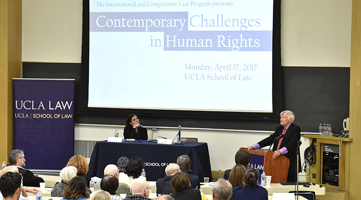 """Speaker at a podium presents to a lecture hall with """"Contemporary Challenges in Human Rights"""" on the screen behind him"""