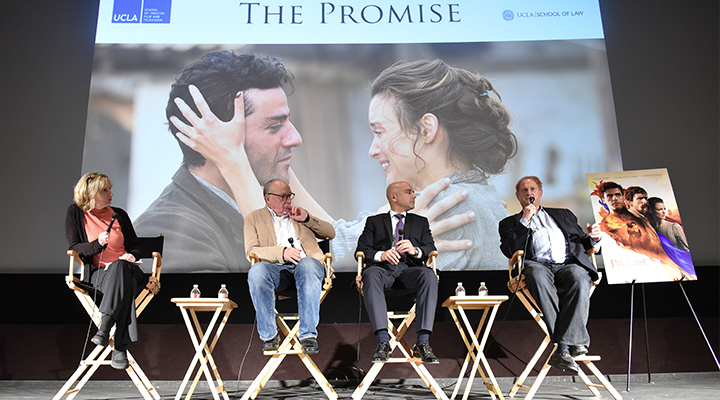 Four panelists sit on stage in front of a screenshot from The Promise film