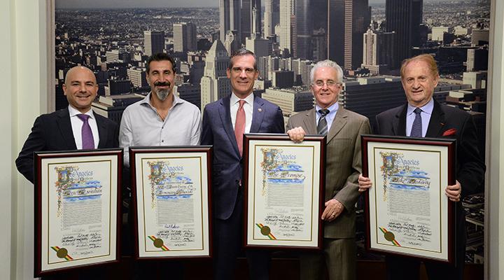 Five men hold up framed proclamations