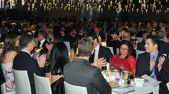 Attendees applaud at long tables under floating candle lighting