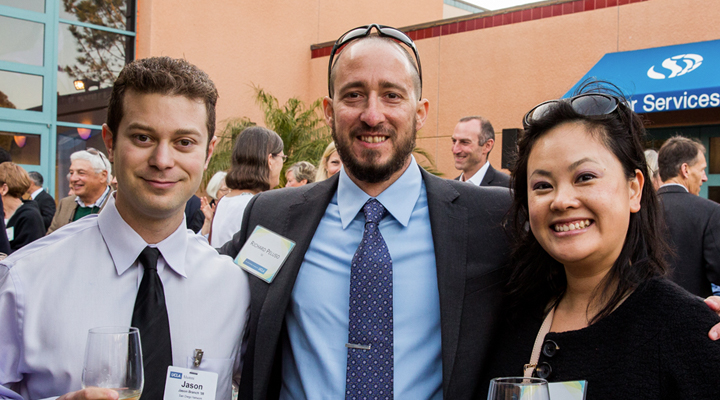 Three event attendees pose in the outdoor courtyard during the cocktail reception