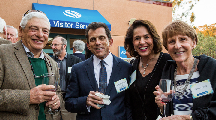 Four event attendees pose in the outdoor courtyard during the cocktail reception
