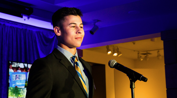 Student allows himself a small smile as he stands before the stage microphone