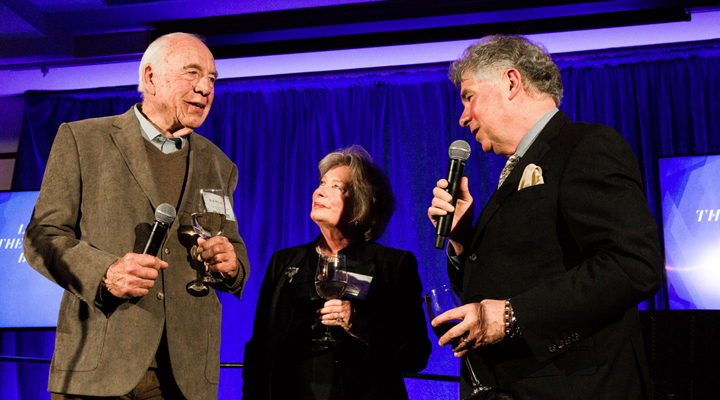 Three donors stand onstage to give a celebratory toast
